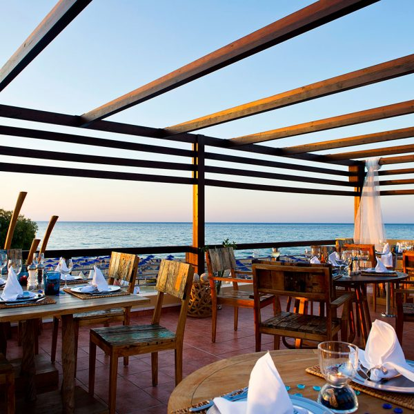 Sea view dining tables on the veranda by the beach at Almyra Fish & Sushi Restaurant close to Chania