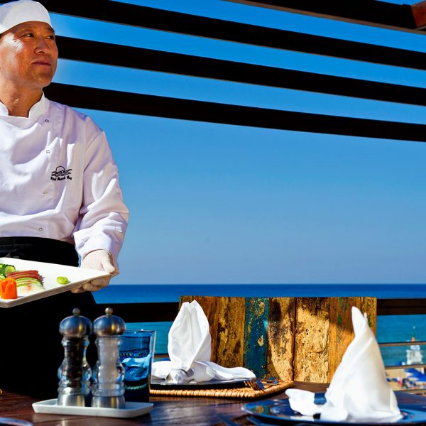 Almyra Restaurant chef holds a sushi dish in front of a view of the sea in Georgioupolis, Chania