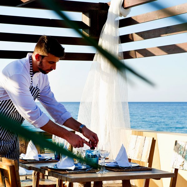 A waiter tends to a table at Almyra fish & sushi restaurant by the sea in Georgioupolis, Chania