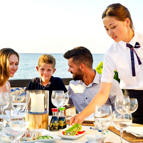 Almyra Fish & Sushi Restaurant waitress serves a family enjoying their meal by the sea in Crete