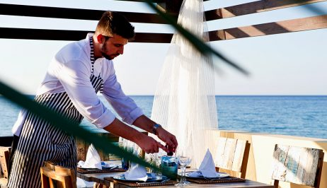 A waiter at Almyra Fish & Sushi Restaurant near Rethymno prepares a dining table for a meal.